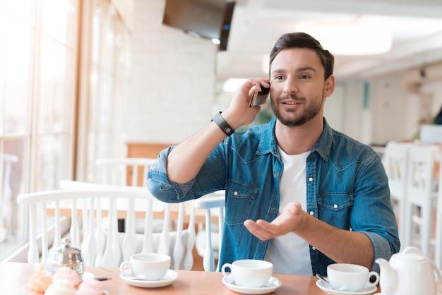 O cara está falando ao telefone em um café. Foto Premium