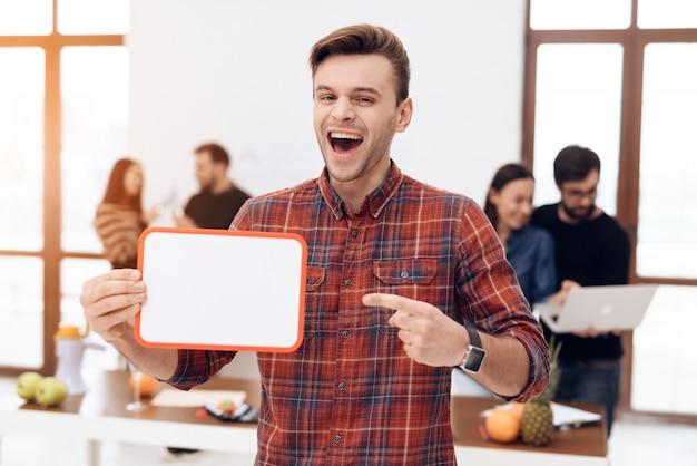O cara está segurando uma placa branca. Foto Premium