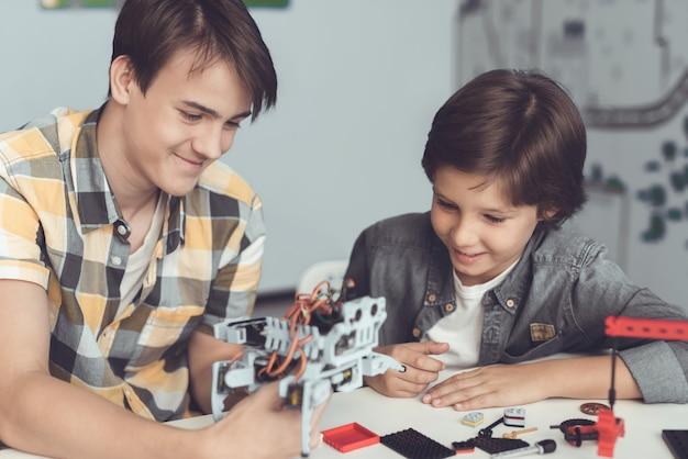 O cara mostra ao menino como o robô está organizado Foto Premium