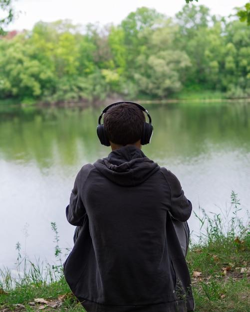 O cara na margem do rio ouvindo música. longe da cidade circundante. ouça fones de ouvido com música Foto Premium