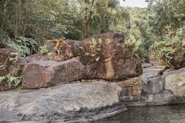 O cara pula de uma pedra na água Foto gratuita