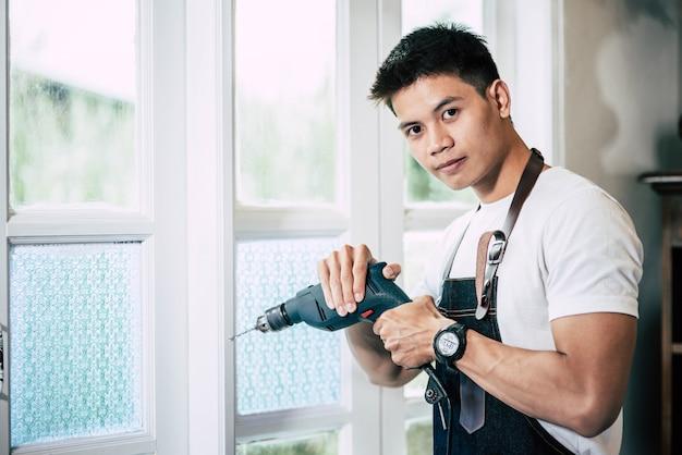 O carpinteiro segura a broca e perfura a janela. Foto gratuita