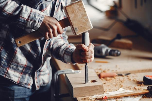 O carpinteiro trabalha com uma árvore Foto gratuita