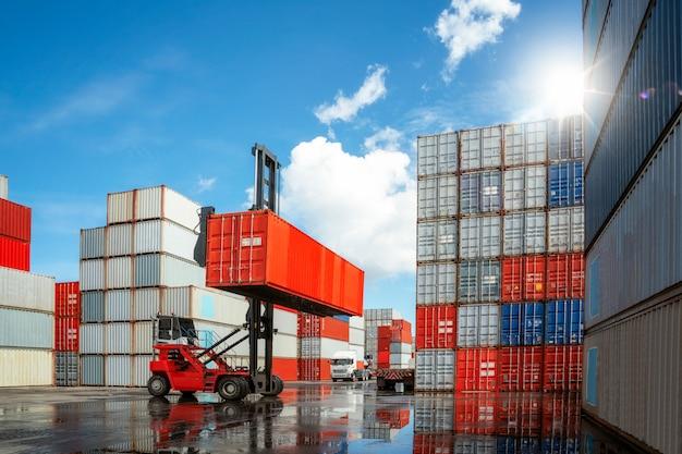 O carro do guindaste move e leva a caixa do recipiente da carga da pilha do recipiente ao caminhão no depósito da caixa do recipiente conpany, esta imagem pode usar-se para o conceito do negócio, do logitic, da importação e da exportação. Foto Premium
