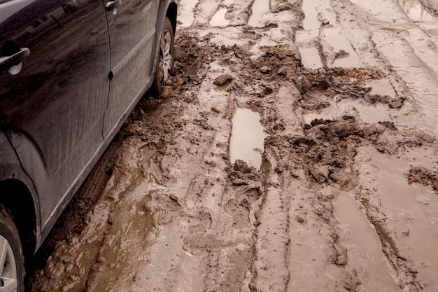 O carro está preso em uma estrada ruim na lama Foto Premium