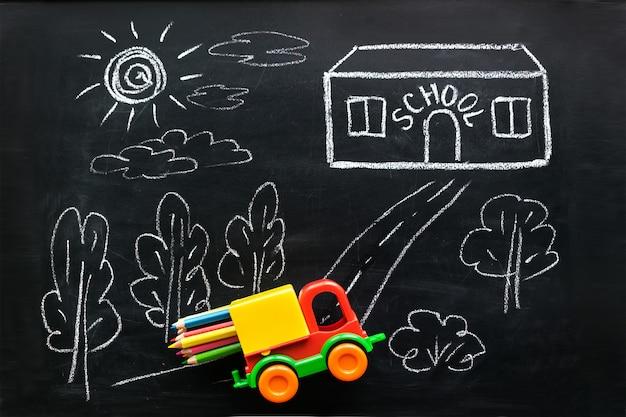 O carro vermelho e amarelo do brinquedo leva lápis coloridos à casa da escola Foto Premium