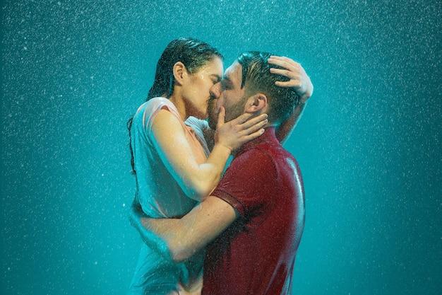 O casal apaixonado se beijando na chuva em um fundo turquesa Foto gratuita