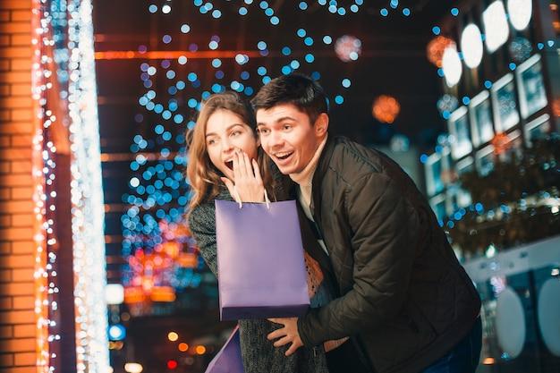 O casal feliz com sacos de compras, aproveitando a noite na cidade Foto gratuita