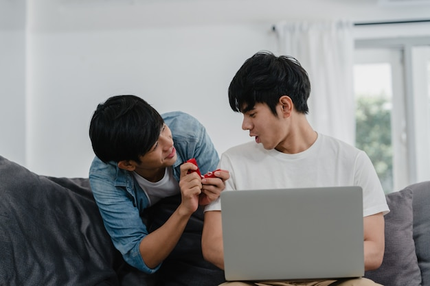 O casal gay asiático novo propõe na casa moderna, o sorriso feliz dos homens coreanos adolescentes de lgbtq tem o tempo romântico ao propor e a surpresa do casamento veste a aliança de casamento na sala de visitas na casa. Foto gratuita