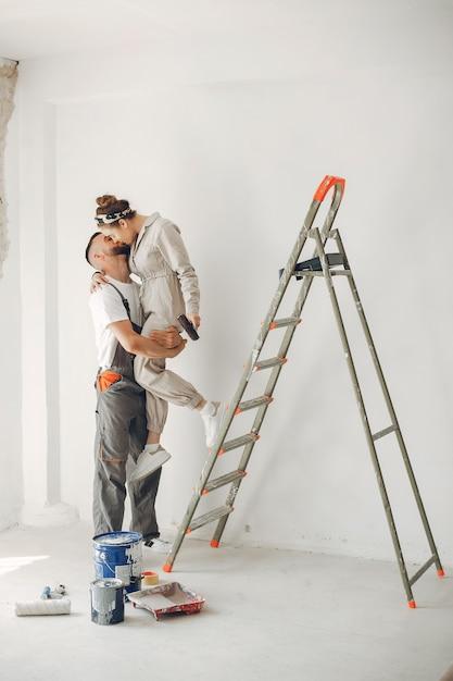 O casal jovem e bonito repara o quarto Foto gratuita