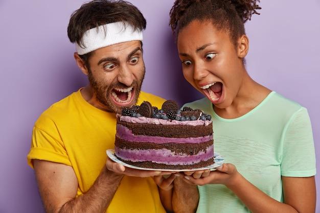 O casal mantém a boca bem aberta, olha para um bolo delicioso, sente a tentação de comer um prato doce, usa camisetas casuais Foto gratuita