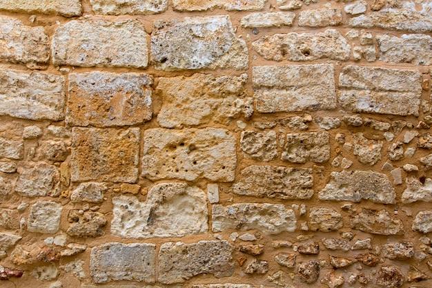 O castelo de menorca stonewall a textura da parede de alvenaria do ashlar Foto Premium