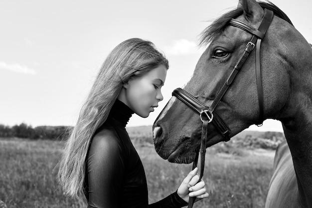 O cavaleiro da menina fica ao lado do cavalo no campo. retrato da moda Foto Premium