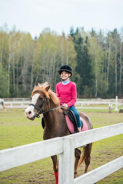 O cavalo de equitação novo do desportista na mostra equestre salta a competição. menina adolescente, passeio um cavalo Foto Premium