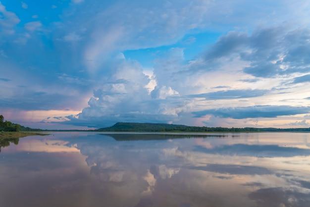 O céu bonito da noite nubla-se no por do sol no lago calmo. Foto Premium