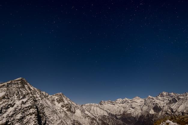 O céu estrelado acima dos alpes no inverno sob o luar Foto Premium
