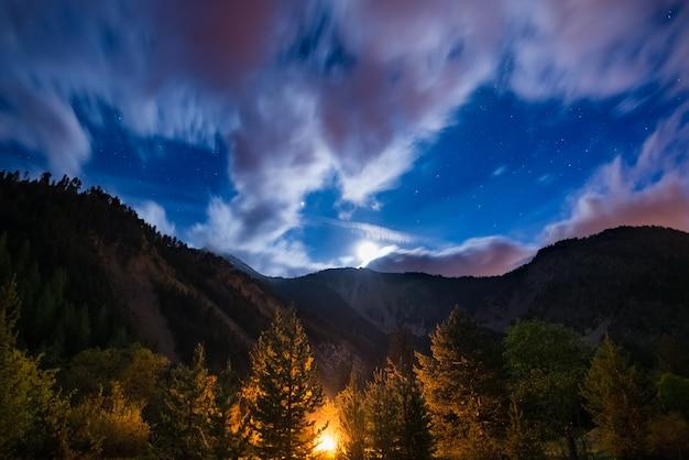 O céu estrelado com nuvens de movimento borrado e luar brilhante, capturado da floresta de lariço, brilhando pelo fogo ardente. paisagem de noite expansiva nos alpes europeus. aventura na natureza. Foto Premium