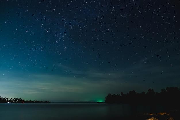 O céu estrelado e a paisagem marinha à noite Foto Premium