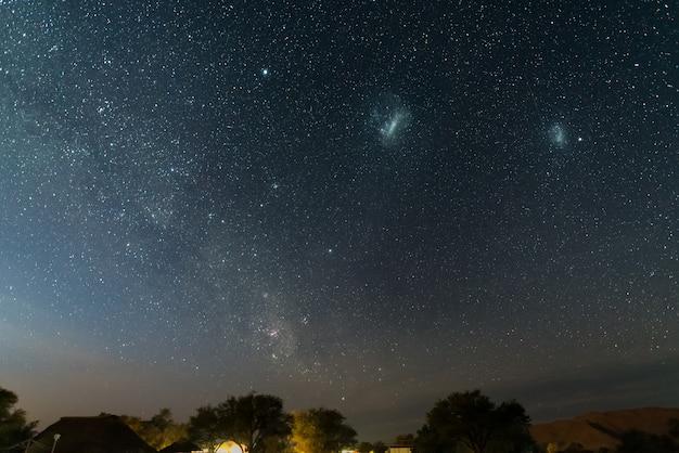 O céu estrelado e as majestosas nuvens de magalhães, excepcionalmente brilhantes, capturadas na áfrica. Foto Premium