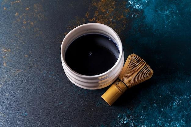 O chá azul do matcha em uma bacia e o bambu chasen no fundo azul, vista superior. Foto Premium