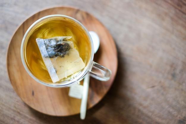 O chá de lavanda quente em vidro servir com colher de pau e pires Foto Premium