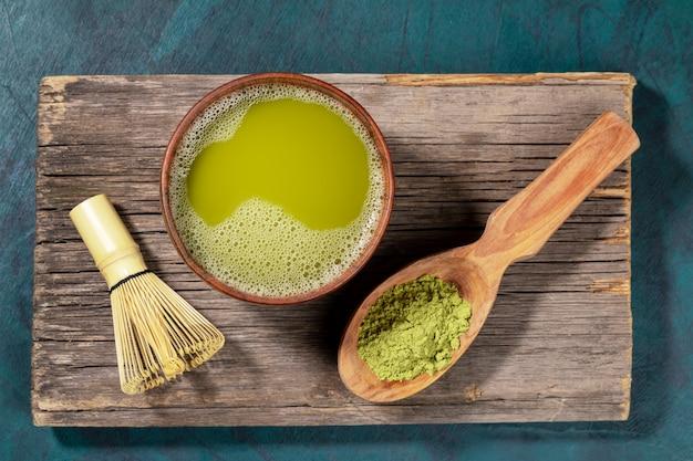 O chá verde japonês do matcha no copo de madeira, o pó do matcha na colher de madeira e o batedor de ovos de bambu na placa de madeira velha. vista do topo. Foto Premium