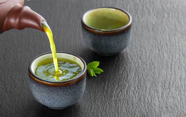 O chá verde quente é despejado do bule na tigela azul Foto gratuita
