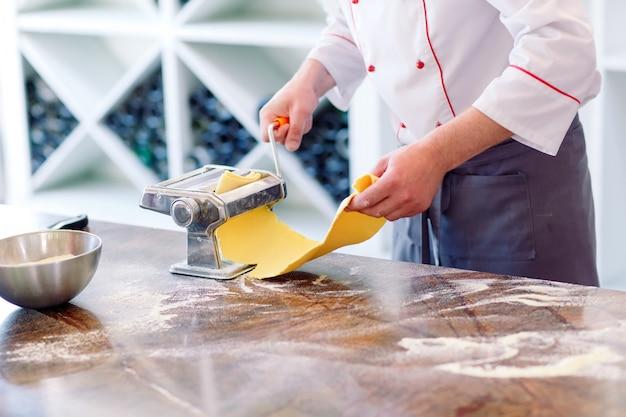 O chef prepara a pasta para os visitantes. Foto Premium
