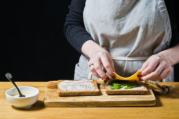 O chef prepara um sanduíche de pão preto, coloca as folhas de rúcula na torrada. Foto Premium