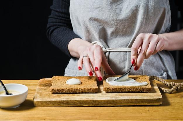 O chef prepara um sanduíche de pão preto, esfrega o molho na torrada. Foto Premium