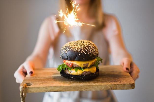 O chefe está segurando uma tábua de madeira com um hambúrguer preto. Foto Premium
