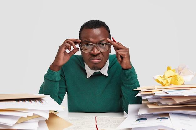 O chefe estressante tem dor de cabeça, expressão de desagrado, tem que pagar contas, tem muitas contas, estuda contabilidade no trabalho Foto gratuita