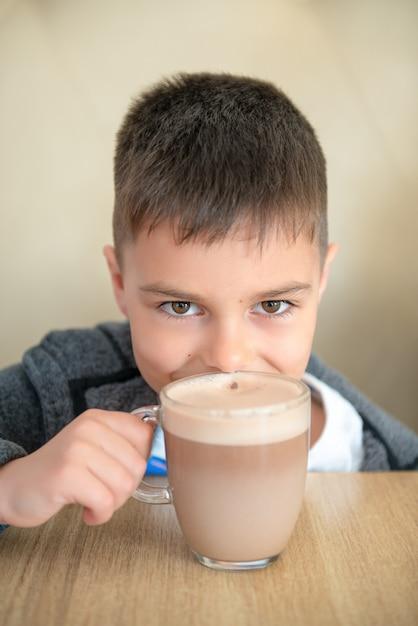 O chocolate caucasiano do menino no café, sorriso e olha a câmera. Foto Premium