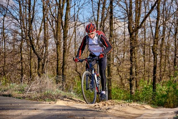 O ciclista dos esportes monta ao longo de uma fuga na floresta em um dia ensolarado da mola. Foto Premium