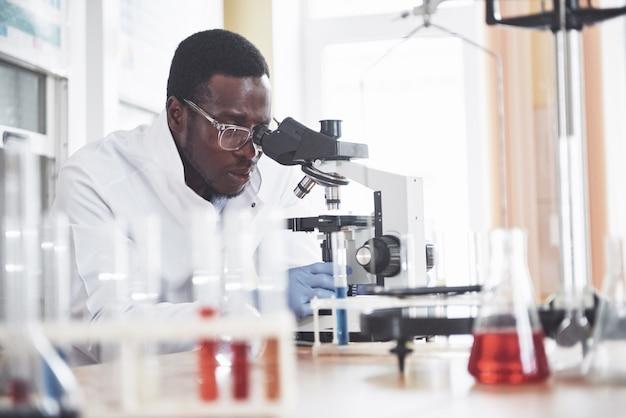 O cientista trabalha com um microscópio em um laboratório conduzindo experimentos e fórmulas. Foto gratuita