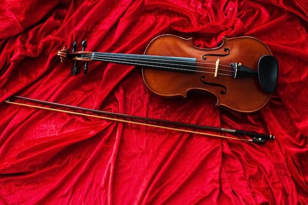 O clássico violino e arco colocar no pano vermelho fundo, mostrar detalhes do instrumento Foto Premium