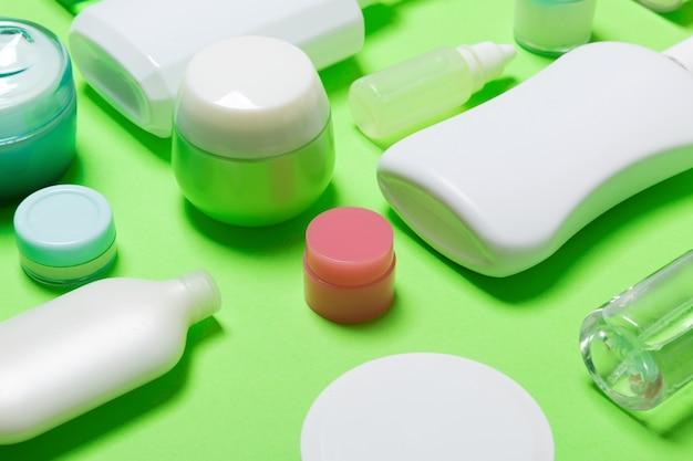 O close-up ajustou frascos e frascos de tamanhos diferentes para produtos cosméticos no fundo verde. rosto e corpo cuidados copyspace Foto Premium