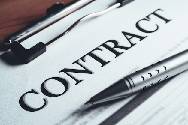 O close-up da pena de prata pôs sobre os papéis do acordo de política do contrato. assinatura de contrato legal. Foto Premium