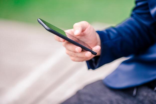 O close up das mãos masculinas está guardando o telefone celular fora na rua. homem usando smartphone móvel. Foto Premium