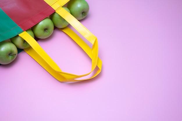 O close up de maçãs verdes no plasti reutilizado multicolorido ensaca. publicidade em campanha de saco reciclado e conceitos de vida saudável. fundo magenta. Foto Premium