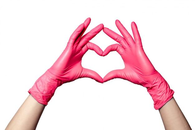 O close up de uma mão nas luvas cor-de-rosa médicas de borracha do látex dobrou-se em um sinal do coração. isolado no fundo branco Foto Premium