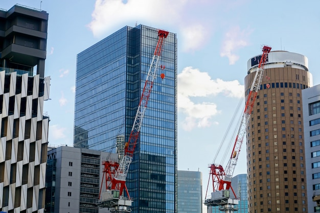 O close up que iça cranes o trabalho na opinião da paisagem da cidade e no prédio de escritórios de vidro com céu azul e fundo sedoso da nuvem. Foto Premium