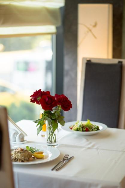 O close up seletivo vertical disparou em rosas vermelhas em cima da mesa perto de pratos cheios de comida na mesa Foto gratuita