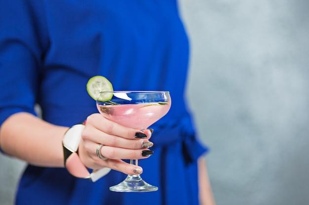 O cocktail exótico e mãos femininas Foto gratuita
