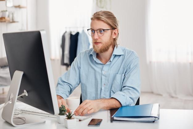 O comerciante masculino sério com cabelo louro, barba, vestindo óculos e camisa azul, prepara o relatório financeiro sobre a renda da empresa, digitando no teclado do computador, senta-se contra o interior moderno e leve do escritório. Foto gratuita