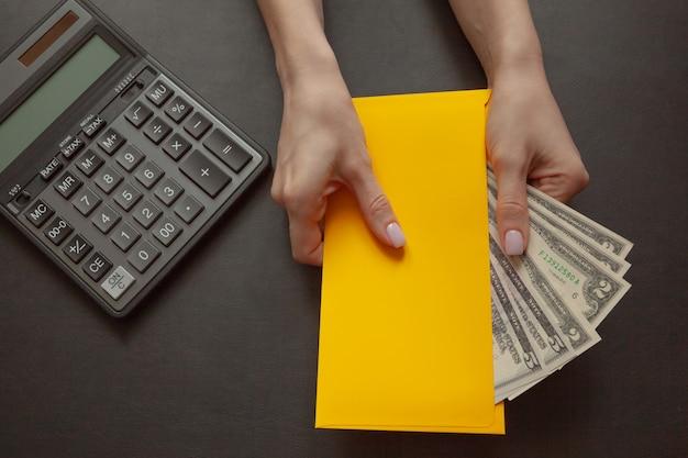 O conceito de bem-estar financeiro, a garota na mão dela segura um envelope amarelo com dinheiro. Foto Premium
