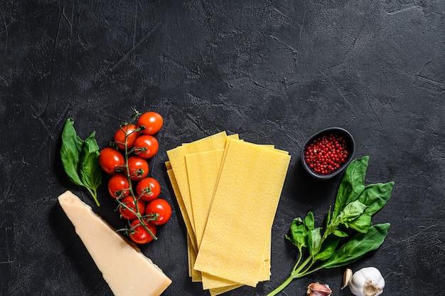 O conceito de cozinhar lasanha. ingredientes, folhas de lasanha, manjericão, tomate cereja, parmesão, alho, pimenta. fundo preto. vista do topo. espaço para texto Foto Premium