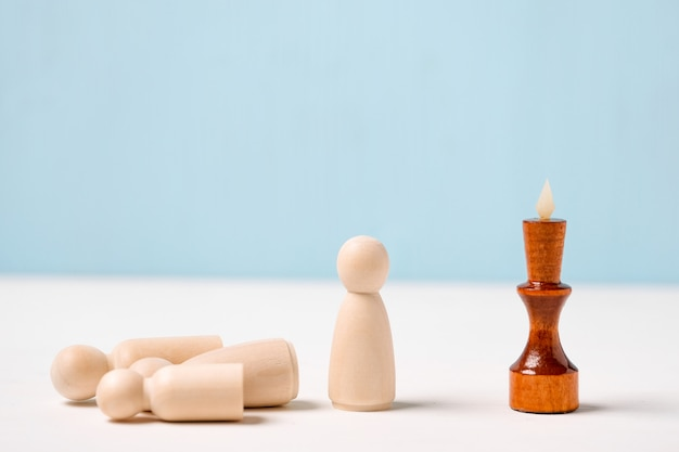 O conceito de demissão de funcionários. a figura do rei de madeira sobre um fundo azul olha para as figuras. Foto Premium