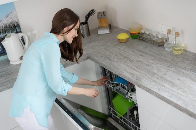 O conceito de lavar pratos modernos, uma mulher puxa pratos limpos da máquina de lavar louça na cozinha branca Foto Premium
