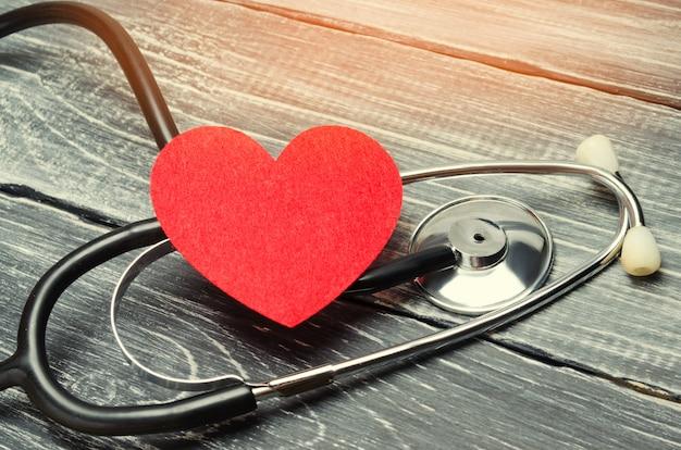 O conceito de medicina de família e seguro. estetoscópio e coração em um fundo de madeira Foto Premium